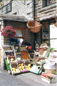 picture of a traditional English greengrocers shop selling fruit and vegetables.  The fruit and vegetables for sale usually extended onto the pavement outside the shop.